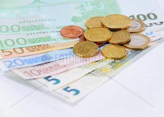 Euroscheine und Muenzen mit weissem Hintergrund