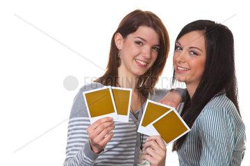 Junges lachendes Maedchen haelt ein Foto in der Hand