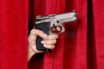 Eine Revolver wird von einer Frauenhand durch einen roten Vorhang geschoben