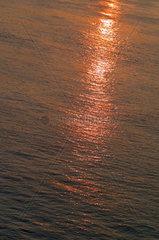 Untergehende Sonne spiegelt sich in einem Fluss