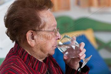 Alte Frau trinkt Wasser aus einem Glas