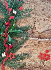 Rustikaler Hintergrund mit Stechpalmen und Tannenzweigen