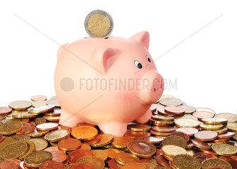 Sparschwein mit 2 Euro Muenze in einer Flaeche aus Euro Muenzen vor weissem Hintergrund