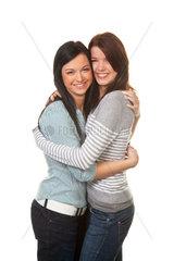 Zwei junge Maedchen umarmen sich freudig und vertragen sich