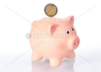 Sparschwein mit 2 Euro Muenze vor weissem Hintergrund