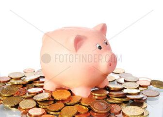 Sparschwein in einer Flaeche aus Euro Muenzen vor weissem Hintergrund