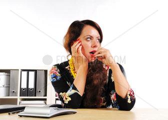 Sekretaerin sitzt am Schreibtisch mit Kugelschreiber im Mund