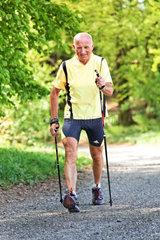 Ein Senior trainiert fuer Fitness beim Nordic walken