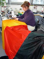 Frau naeht eine Deutschlandfahne