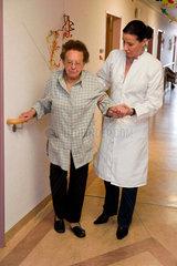 Alte kranke Frau und Pflegerin im Altersheim