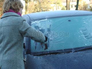 Frau kratzt Eis von der Windschutzscheibe