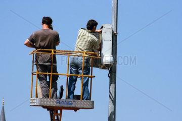 Elektriker mit Strassenbeleuchtung auf Hebebuehne