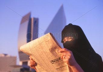 Arabische  verschleierte Frau liest Wirtschaftszeitung