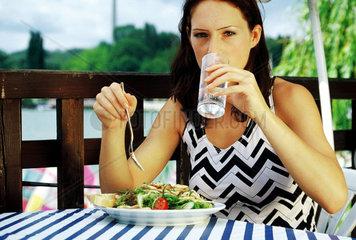 Junge Frau mit Mineralwasser und Salat