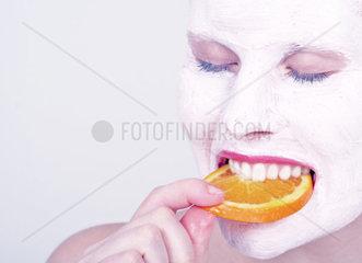 Frau beisst in eine Orangenscheibe