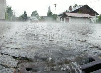 Schwerer Regenfall mit ueberfluteter Strasse