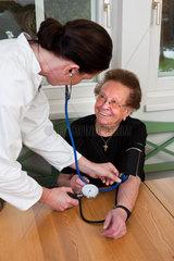 Eine ssrztin misst einer Patientin den Blutdruck