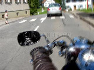 Motorradfahrer und Kind auf Schutzweg