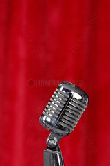 Silbernes Mikrofon vor einem rotem Vorhang