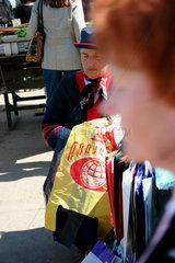 Lettland/Latvia/Riga. Markt von Riga. Eine Altere Frau beim Verkauf von Plastik Einkausftueten.