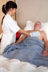 Ein Pfleger waescht einen Patienten