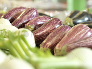 Eggplants with other vegetables on display at supermarket
