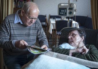 Mann liest seiner kranken Frau vor