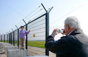 Touristin posiert am Sperrzaun zum G8-Gipfel