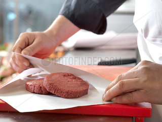 Butcher wrapping beef patties in wax paper  cropped