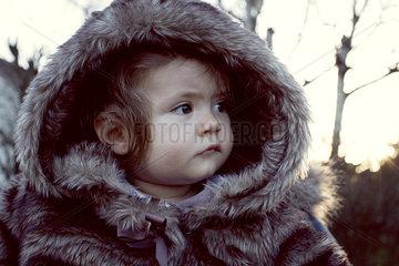 Baby wearing fur coat outdoors  portrait