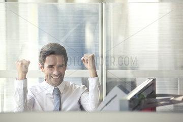 Businessman watching sports match on computer at work