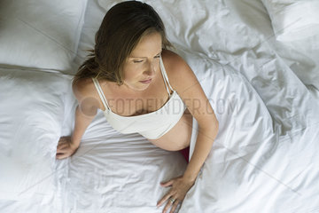 Preganant woman waking up in bed