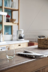 Empty wine glass and newspaper left on kitchen counter
