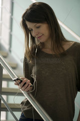 Woman using cell phone with hands-free device