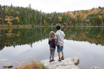 Young brother and sister looking at peaceful lake  rear view