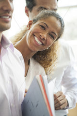 Businesswoman leaning out between two colleagues  smiling cheerfully