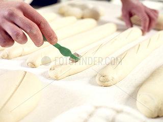 Baker scoring bread dough  cropped