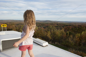 Little girl standing on top of motor home  looking at scenic view