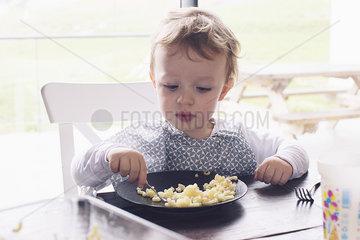 Little boy eating macaroni