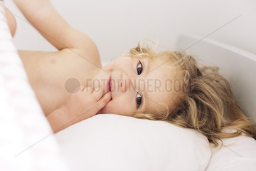 Little girl lying down with finger in mouth  portrait