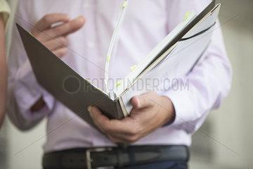 Office worker flipping through binder