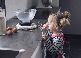 Little girl holding whisk in kitchen