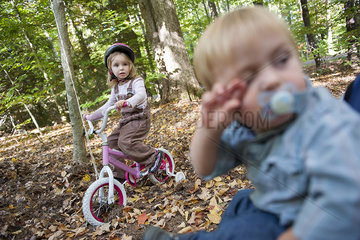 Little girl riding bike in wooded area