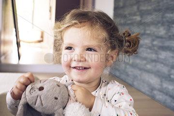 Little girl holding stuffed toy  smiling  portrait