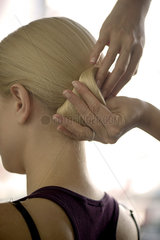 Hairdresser arranging woman's hair in a chignon  cropped