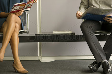 Man and woman sitting in waiting room  low section