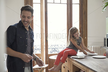 Girl helping father set table for family meal