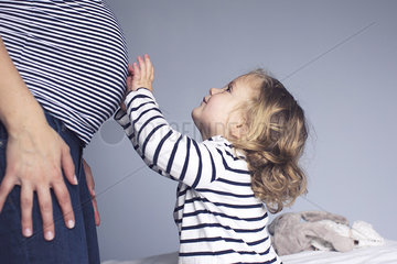 Little girl touching mother's pregnant stomach  cropped