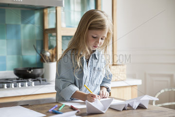Little girl coloring in kitchen