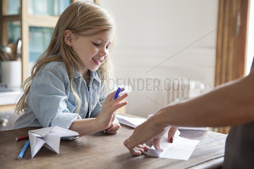 Little girl learning how to make paper airplane